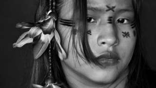 Black and white portrait of a girl with painted designs on her face