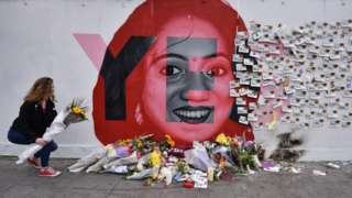 A young woman leaves flowers at the Savita Halappanavar mural in Dublin