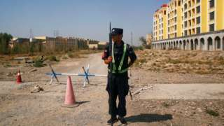 """Chinese police officer outside what is formally known as a """"vocational educational facility"""" in Xinjiang, China (file pic)"""