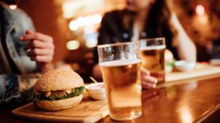 Burger, and pint glasses, with man and woman in background inside a pub