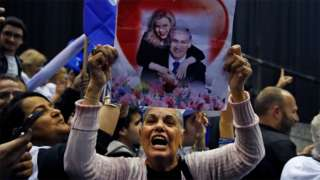 Likud supporter holds up a poster showing Israeli Prime Minister Benjamin Netanyahu and his wife Sara in Tel Aviv (2 March 2020)