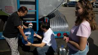 People get containers filled with water from a water tank truck