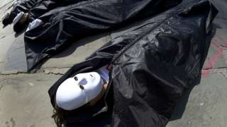 Protesters lay on the sidewalk in body bags near the United Nations in New York