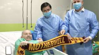Stephen Cameron, face blurred, poses with a Motherwell scarf in hospital