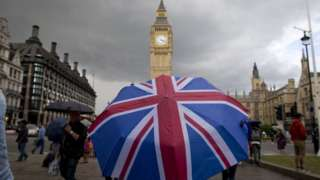 A person holding a union jack umbrella in front of Big Ben