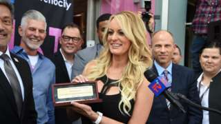 Stormy Daniels shows the key to the city of West Hollywood to photographers
