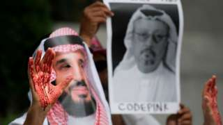 Protester dressed as MBS, with 'blood' on his hands, beside a picture of Khashoggi, in Washington on 8 December 2018