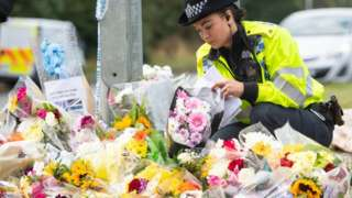 Police officer lays flowers at scene