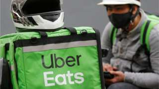 An Uber Eats food delivery courier wearing a protective face mask waits for an order amid the outbreak of the coronavirus disease (COVID-19) in central Kiev, Ukraine May 27, 2020