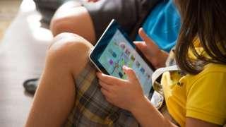 A girl watches cartoons on an iPad