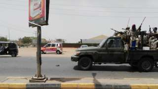 Sudanese security forces drive through a main road linking Omdurman with its twin city Khartoum on 9 JunE