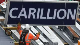 A construction worker guides a Carillion sign being lowered to the ground
