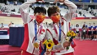 鍾天使(右)、鮑珊菊(左)接受奧運金牌後朝著攝影記者做出心形姿勢(2/8/2021)