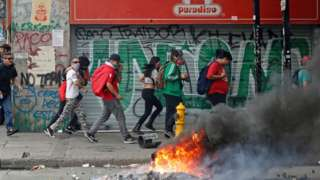Protesters walk quickly past burning debris on the streets of Santiago