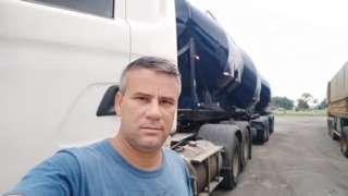 Retrato de Wanderlei Dedeco, um homem branco de meia idade de cabelos grisalhos, com caminhão branco e preto ao fundo
