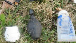A grenade-shaped object is seen next to a tube of lubricant and a USB cord in place handout image
