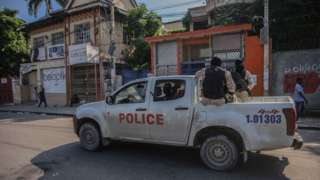 Armed police ride in the back of a truck in Port-au-Prince on 18 October