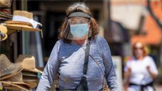 A woman in a mask and face shield is pictured in California