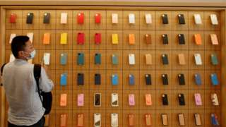 A man stands in front of a wall of iPhones cases in the new Apple flagship store on its opening day in Sanlitun in Beijing, China, July 17, 2020.