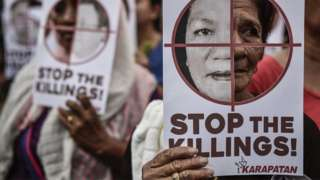 Protesters hold up pictures of victims of extrajudicial killings during Human Rights Day protests in Manila, Philippines