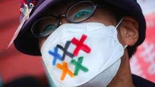 일본의 한 시민이 도쿄올림픽 개최를 반대하는 시위로 오륜기 색이 들어간 마스크를 쓰고 있다