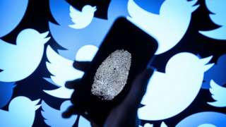 A thumbprint is displayed on a mobile phone as the logo for the Twitter social media network is projected onto a screen on August 09, 2017 in London, England