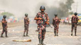 Border Guards Bangladesh (BGB) personnel secure a highway as activists from Hefazat-e Islam block a road during a nationwide strike following deadly clashes with police over Indian Prime Minister Narendra Modis visit, in Narayanganj, about 16 kms southeast of Dhaka on March 28, 2021.
