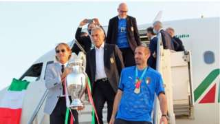 Italy captain Giorgio Chiellini (R) and head coach Roberto Mancini (L) hold the trophy after the team's plane landed