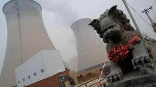 중국의 공장 굴뚝 앞에 사자상이 서 있다