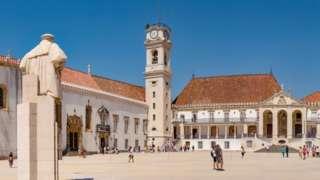 Torre da Universidade de Coimbra diante de pátio com pessoas caminhando em um dia de sol; há uma estátua de costas