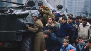 Romanian soldiers and civilians take cover behind a tank in Bucharest's Palace Square in December 1989