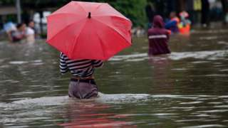 Person standing with umbrella in flooded street