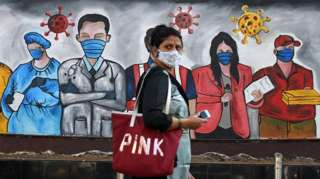 woman wearing a mask walks past a graffiti raising awareness about wearing of facemasks to avoid the risk of the COVID-19 coronavirus in Mumbai