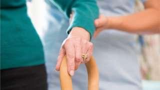Woman helping elderly person