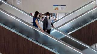 People wearing face masks on an escalator in a shopping centre in Japan.