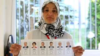 A returning officer shows a voting paper for the Presidential and General elections in Turkey, at a polling station at Turkey Consulate-General in Berlin on June 07