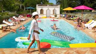 People relaxing by a French swimming pool