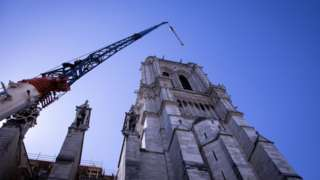 A crane looms over Notre-Dame cathedral in Paris