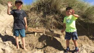 Flynn, 7, and Teddy, 4, with signs in sand dunes