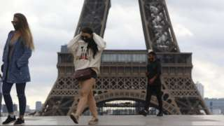 People wear face masks near the Eiffel Tower in Paris, France, 23 September 2020