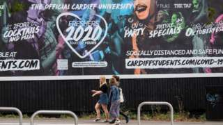 Students walking past a Freshers 2020 billboard in Cardiff