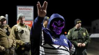 "An attendee wears an alien mask at the gate of Area 51 as an influx of tourists responding to a call to ""storm"" Area 51"