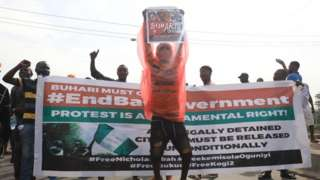 Protester carry placard in front of banner on June 12, 2021 for Lagos