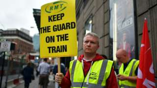 An RMT union member holds up a placard