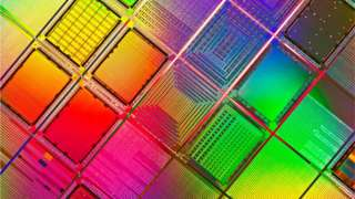Silicon wafers are seen this extreme-close-up file photo, shimmering in a rainbow of colours