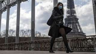 A woman wears a face mask as walks across a footbridge near the Eiffel Tower in Paris, France. Photo: 19 March 2021