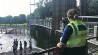 A PCSO looks on as a boy leaps into the water