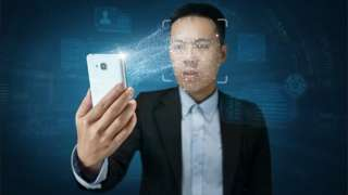 Young modern man in suit holds up a smartphone to his face, enabling facial recognition