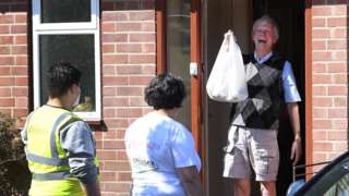 A man receives a shopping bag from mutual aid workers