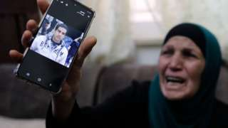 The mother of Iyad Halaq holds up a mobile phone photograph of him (30 May 2020)